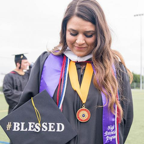 "Chrissy Camilleri '17 stands with her graduation cap that says ""blessed."""