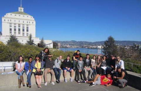 The class gathers on a rooftop terrace at the Oakland Museum of California, with the Alameda County Courthouse and Lake Merritt seen in the background.