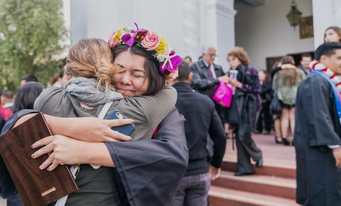 A graduate hugs her friend outside of the Chapel.