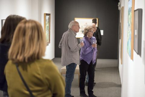 "Members enjoy a preview of artwork in the exhibition ""Feminizing Permanence."""