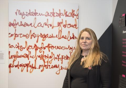 "Artist Diane Rosenblum stands by her work ""Artist Statement"" on view in ""Feminizing Permanence."""