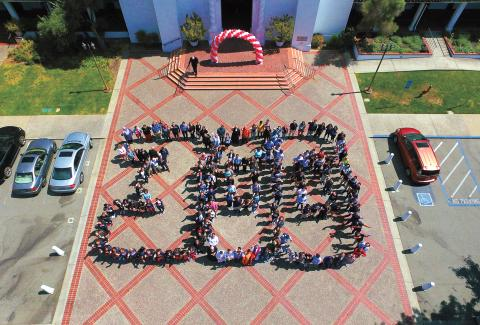 Faculty Staff and students forming the number 300