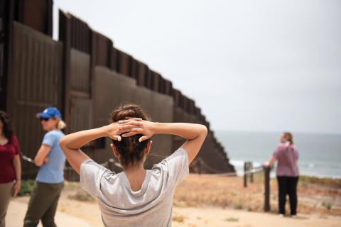 Professor Rebecca Anguiano looks out at the border wall receding into the pacific ocean