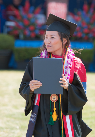 student holding a diploma cover