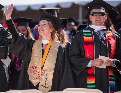 students standing during commencement waving
