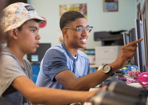 Student showing a child something on a computer