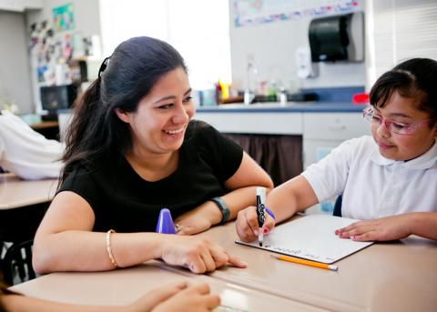 A student smiling while working with a child something in a classroom