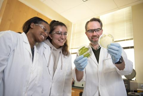 A professor smiling while showing students two different algae samples