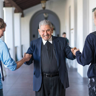 Brother Camillus, FSC fist bumping students