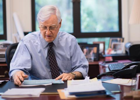 President Donahue looking at papers on his desk