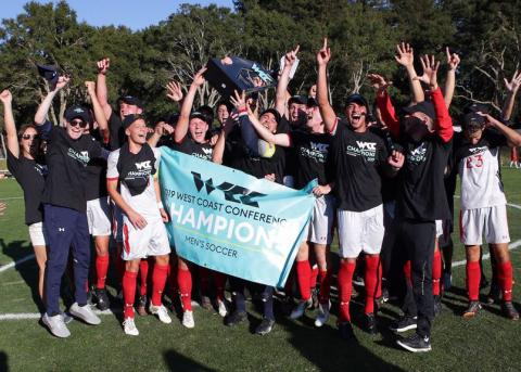 Soccer team cheering and waving a sign after winning WCC Championship
