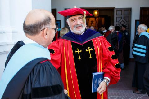 Brother Michael Meister, in full academic regalia, greets Brother Alvaro.