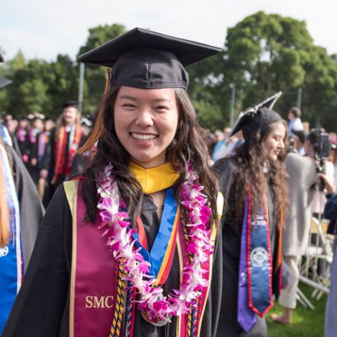 Saint Mary's College Graduate smiling in the camera wearing a lei