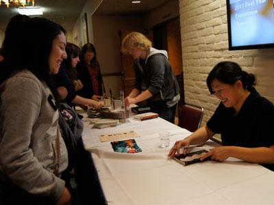Yiyun Li signs a copy of her book, A Thousand Years of Good Prayer, for a student.