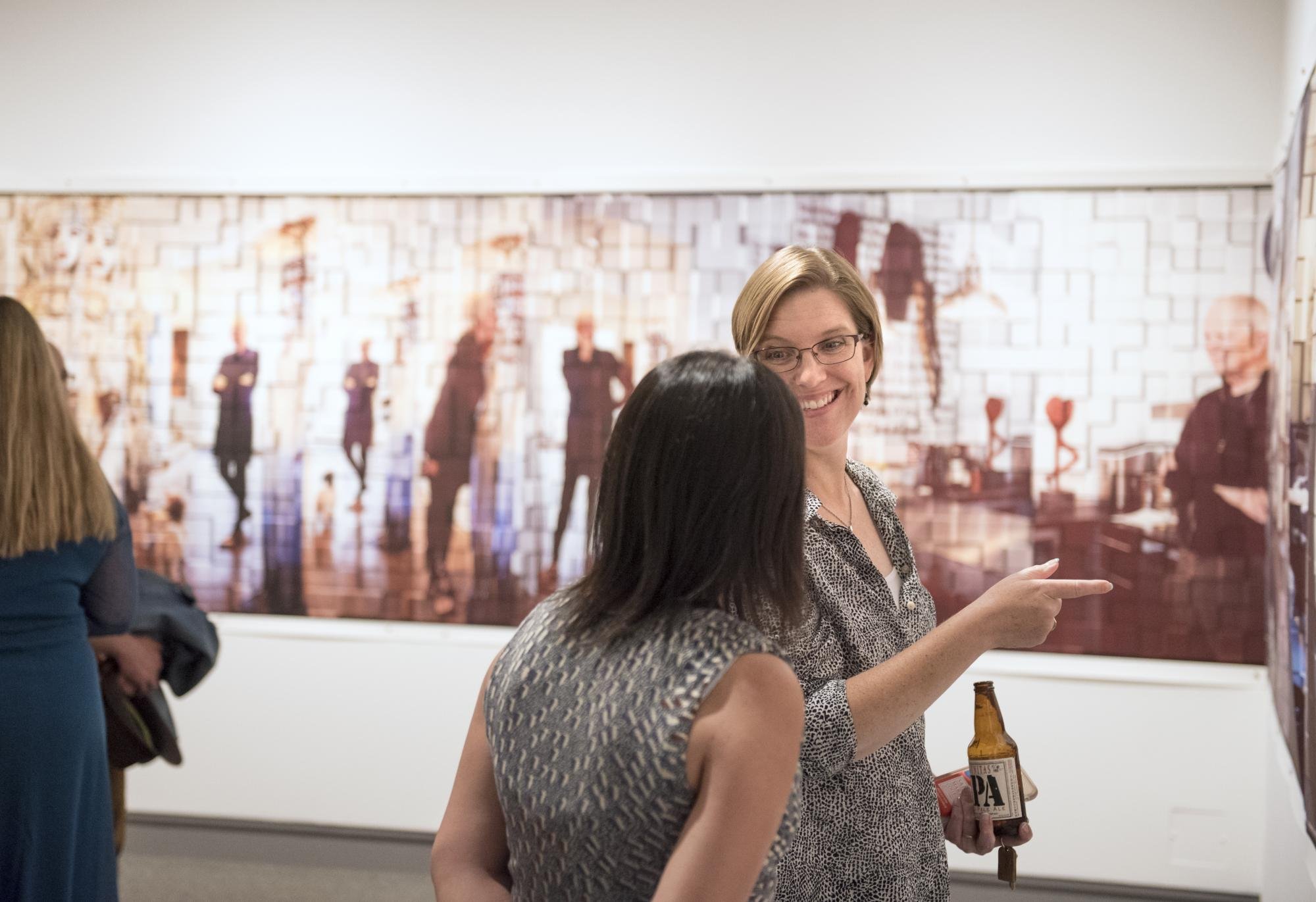 "Visitors interact in the gallery space featuring installation photograph, ""A Studio visit with Judith Kindler"" by Diane Rosenblum and Joe Doyle. Photograph by Haley Nelson."