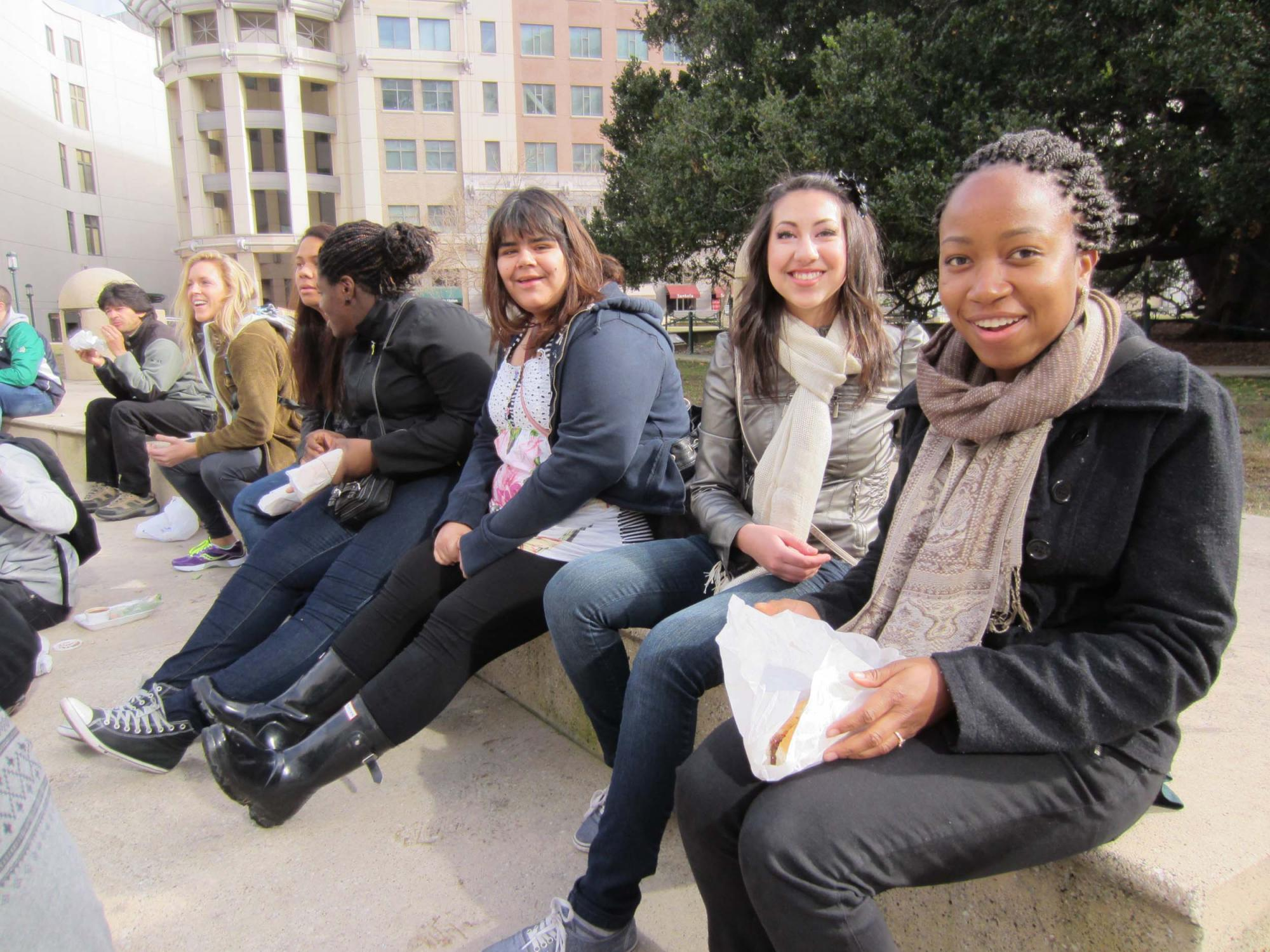 """Students enjoying Vietnamese """"banh mi"""" sandwiches on Frank Ogawa Plaza in front of City Hall."""