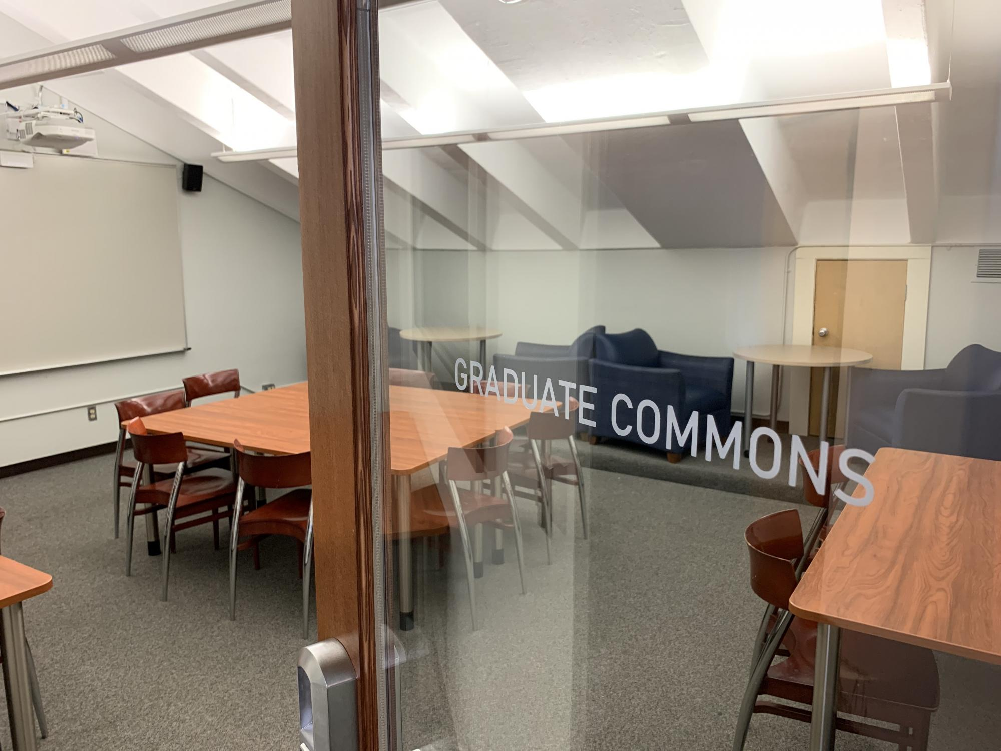 """Photo showing the graduate commons, including tables, chairs, lounge chairs, and a glass door labeled """"graduate commons"""""""