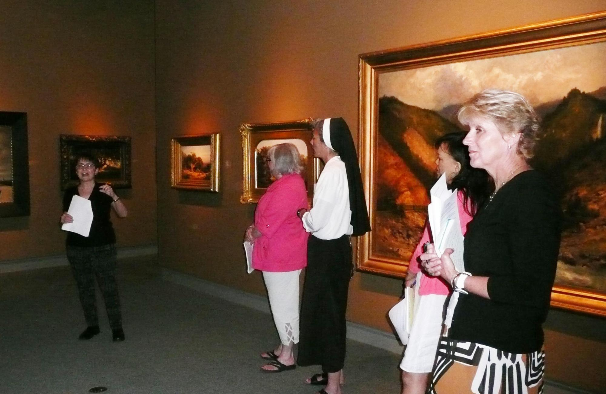 Museum Director Carrie Brewster demonstrated her knowledge of how to hang artworks.
