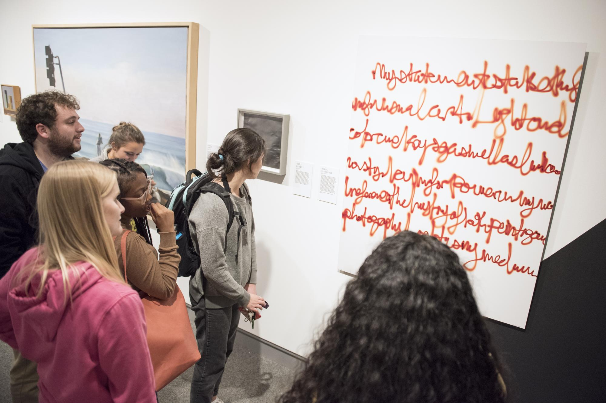 "SMC students engage and view work by artist Diane Rosenblum, featured in the exhibition ""Feminizing Permanence."""