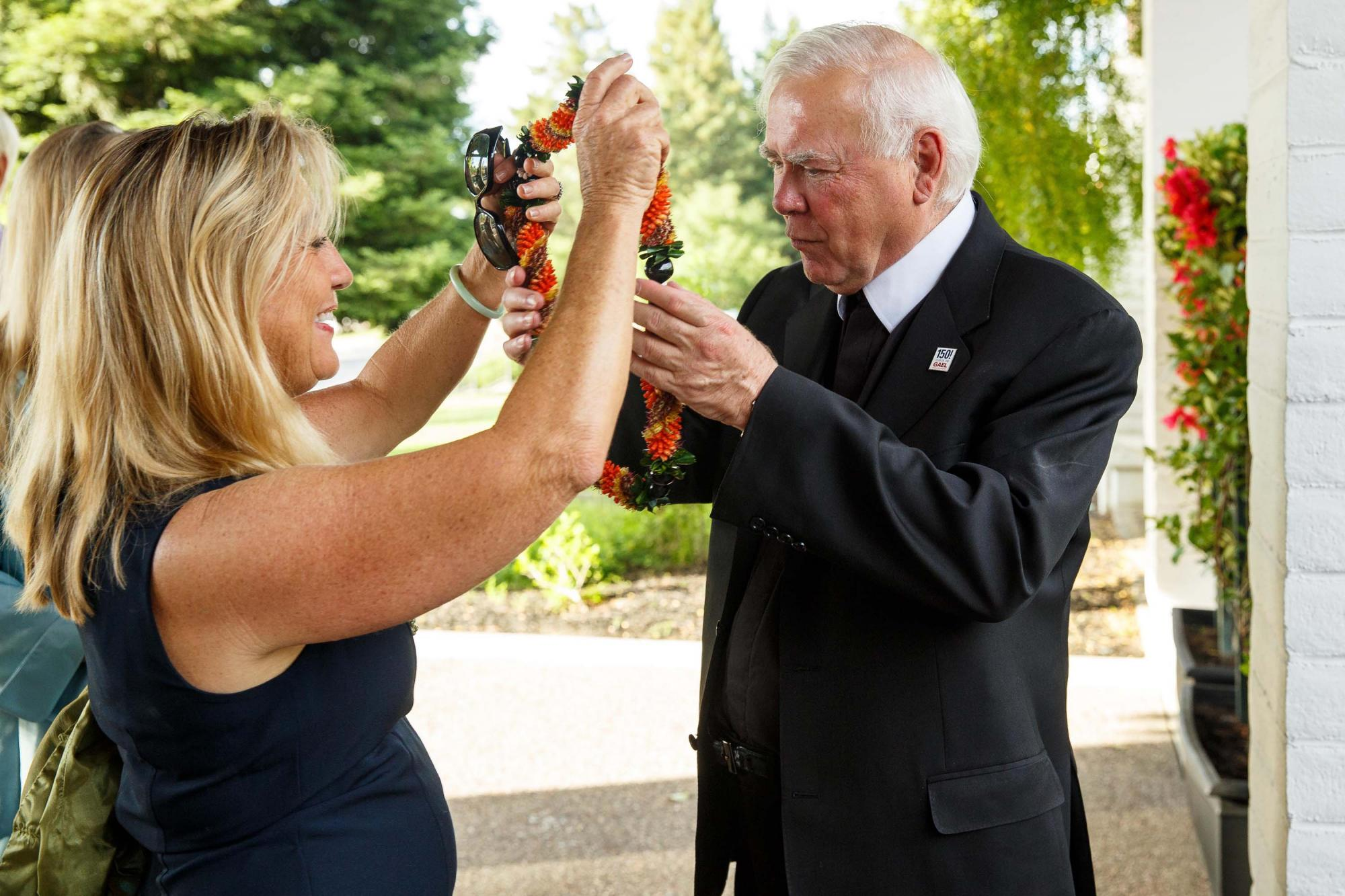 Brother Ron's sister, Maureen Chung, greets him with a lei.