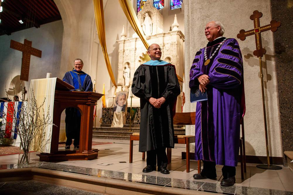 Brother Alvaro accepts the blue hood of his honorary SMC doctorate.