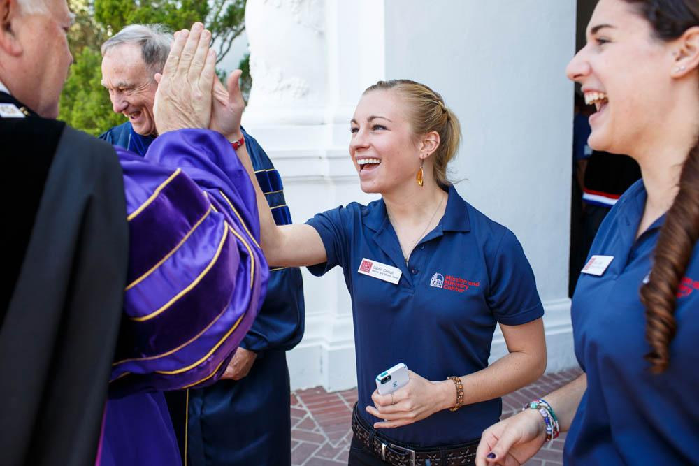 Sophomore Gabbi Carroll gives a high-five to a Brother after Convocation.