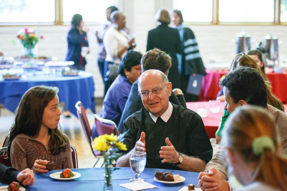 Brother Alvaro talks with members of the SMC community during a reception in the Soda Center after Convocation.