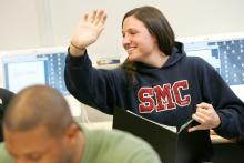 A woman in an SMC hoodie raises her hand in class