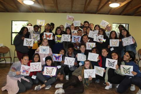 Photo of diversity retreat participants holding pictures of butterflies.