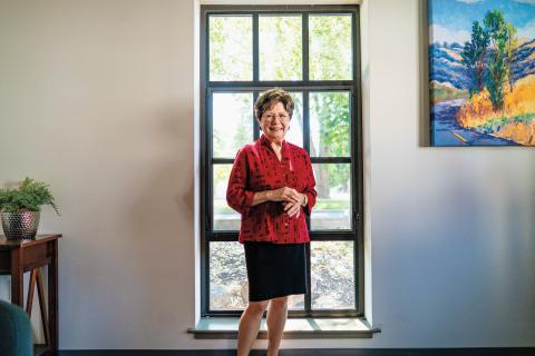 Joan Peterson Standing in front of a window.