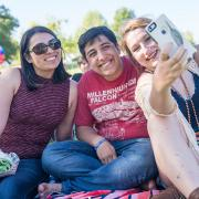 A group of students pose with a cell phone at a concert at the Moraga Commons.