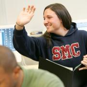 A young woman in an SMC hoodie raises her hand in class