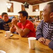 Three male students laugh around a table in Oliver Hall.