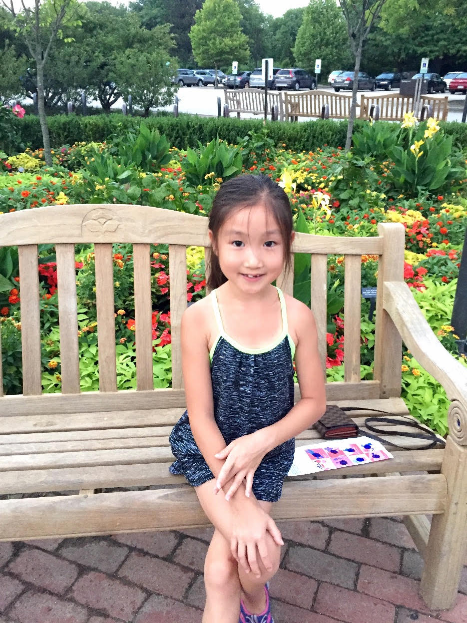 Laura Hu, a ten year old student, sits alone on a wooden park bench in a garden with a parking lot in the far background. Laura is smiling. The garden has various flowing plants and trees in it; identifiable plants include tulips and daffodils.